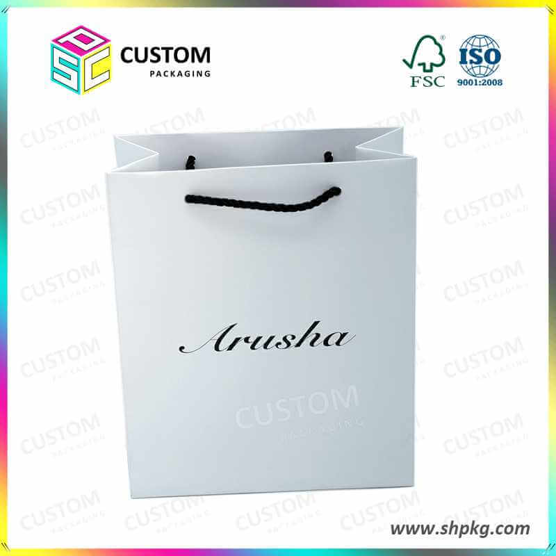 white paper bag with black handle